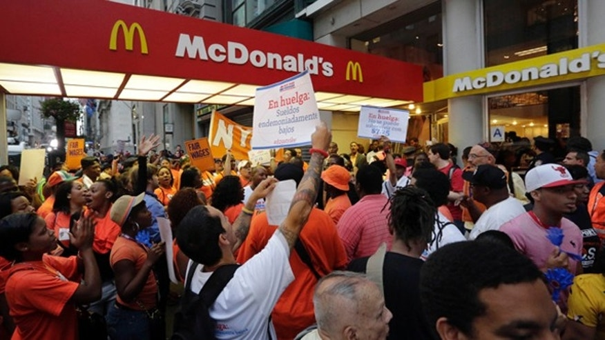 FILE: Aug. 29, 2013: Fast food workers demonstrate outside a McDonald's on New York's Fifth Avenue to get such fast-food chains to pay workers higher wages.
