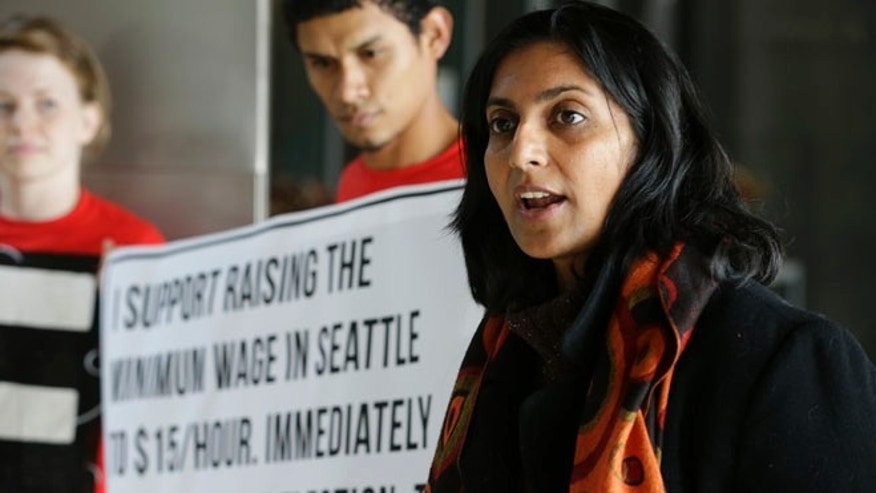 Nov. 4, 2013, Socialist candidate for Seattle City Council Kshama Sawant, right, speaks outside City Council chambers in Seattle about her support for raising the minimum wage to $15 an hour for all workers in the city.