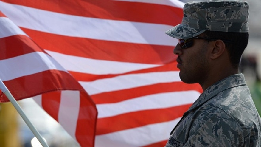 DOVER, DE - SEPTEMBER 29:  A member of the United States Air Force stands on the grid with an American flag prior to the NASCAR Sprint Cup Series AAA 400 at Dover International Speedway on September 29, 2013 in Dover, Delaware.  (Photo by Patrick Smith/Getty Images)