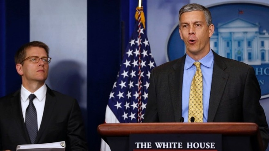 FILE: U.S. Secretary of Education Arne Duncan, right, stands next to White House Press Secretary Jay Carney as he briefs the press about education in the White House Briefing Room in Washington.
