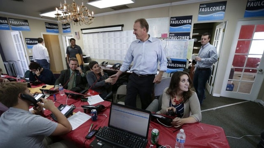 November 19, 2013: San Diego city councilman and Republican candidate for mayor, Kevin Faulconer, center, shakes hands with volunteers making phone calls to voters at his headquarters during mayoral elections in San Diego. (AP Photo)