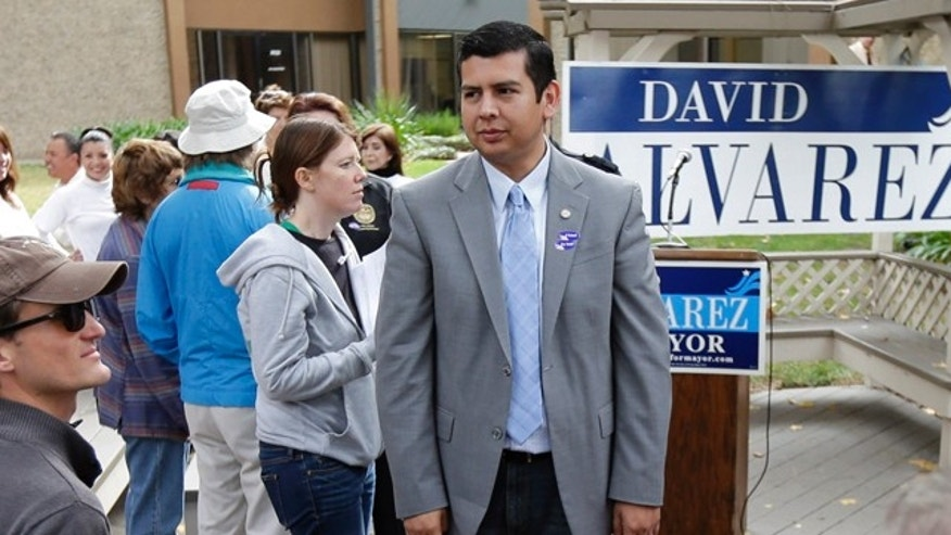 David Alvarez, above center, a San Diego city councilman and Democratic candidate for mayor, looks on as he meets with supporters Tuesday, Nov. 19, 2013, in San Diego. San Diegans head to the polls Tuesday to choose a new mayor, after Bob Filner's resignation amid allegations of sexual harassment has left the city with an interim mayor. (AP Photo/Gregory Bull)