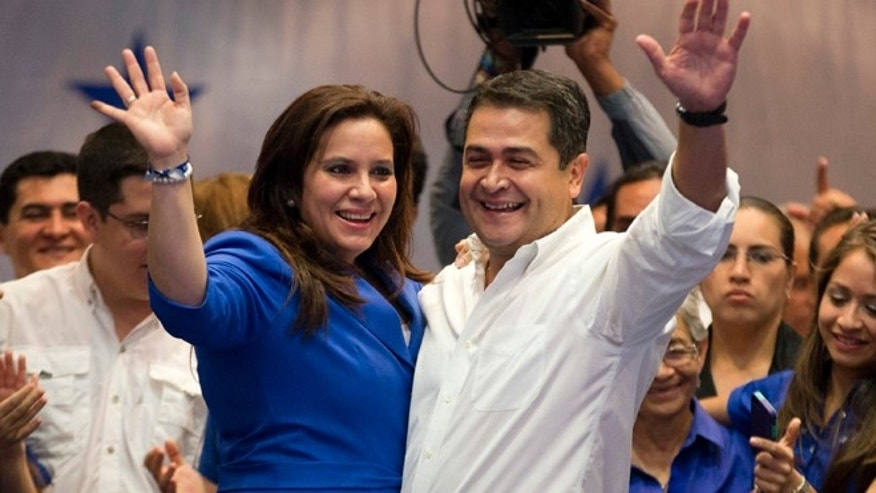 National Party presidential candidate Juan Orlando Hernandez and his wife, Ana Garcia, left, waves to supporters during his victory speech, after partial election results in Tegucigalpa, Honduras, Sunday, Nov. 24, 2013. The electoral court said preliminary results gave Hernandez a comfortable edge over Xiomara Castro, whose husband Manuel Zelaya was overthrown in the military-backed coup.(AP Photo/Eduardo Verdugo)