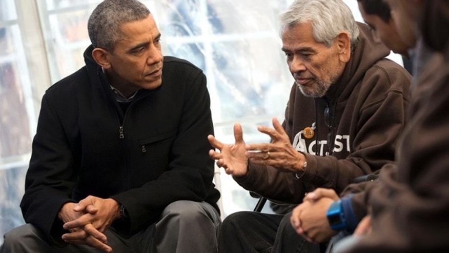 President Obama listens to Eliseo Medina, Secretary-Treasurer of Service Employees International Union, as he meets with individuals who are taking part in Fast for Families on the National Mall in Washington, Friday, Nov. 29, 2013.