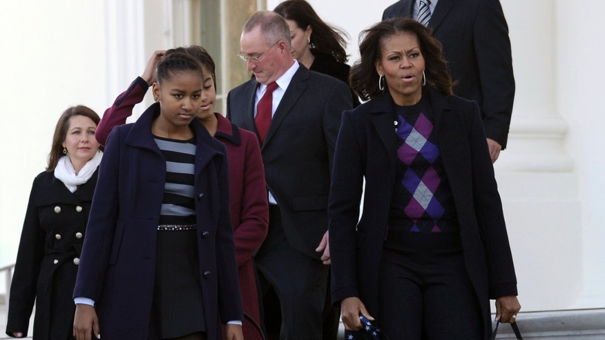 First lady Michelle Obama, right, with daughters Sasha, second from left, and Malia, partially hidden, walk outside to receive the Official White House Christmas Tree at the White House? in Washington, Friday, Nov. 29, 2013. (AP Photo/Susan Walsh)