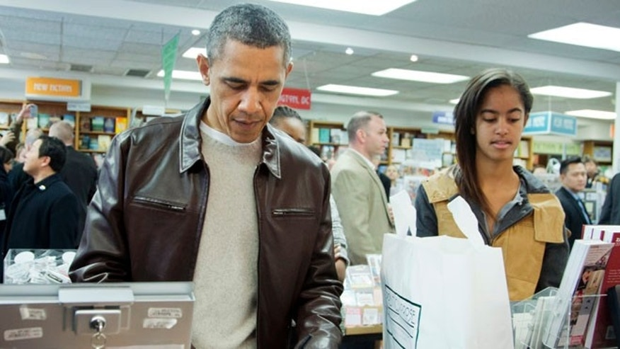 Saturday, Nov. 30, 2013: President Obama, with daughters Sasha, center partially hidden, and Malia, pays for his purchase at the Politics and Prose bookstore in Washington, D.C.