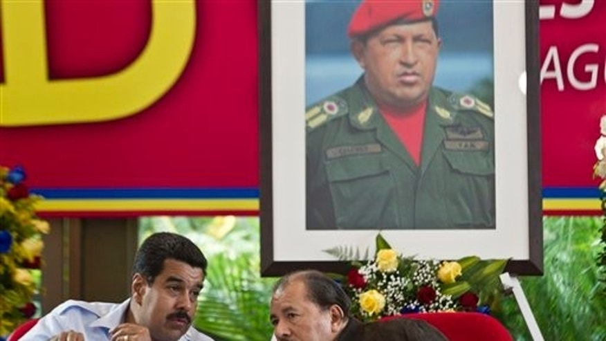 Under a portrait of the late Hugo Chavez, Venezuela's President Nicolas Maduro, left, talks with Nicaragua's President Daniel Ortega during the 8th Petrocaribe Summit in Managua, Nicaragua. (AP Photo/Esteban Felix, File)