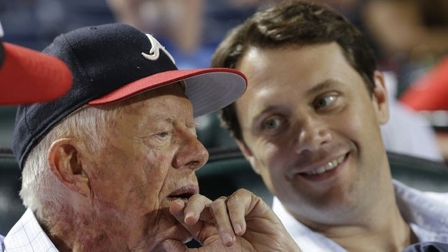 FILE: Aug. 14, 2013:Former President Jimmy Carter and his grandson, Georgia state Sen. Jason Carter, watch an Atlanta Braves baseball game, in Atlanta, Ga.