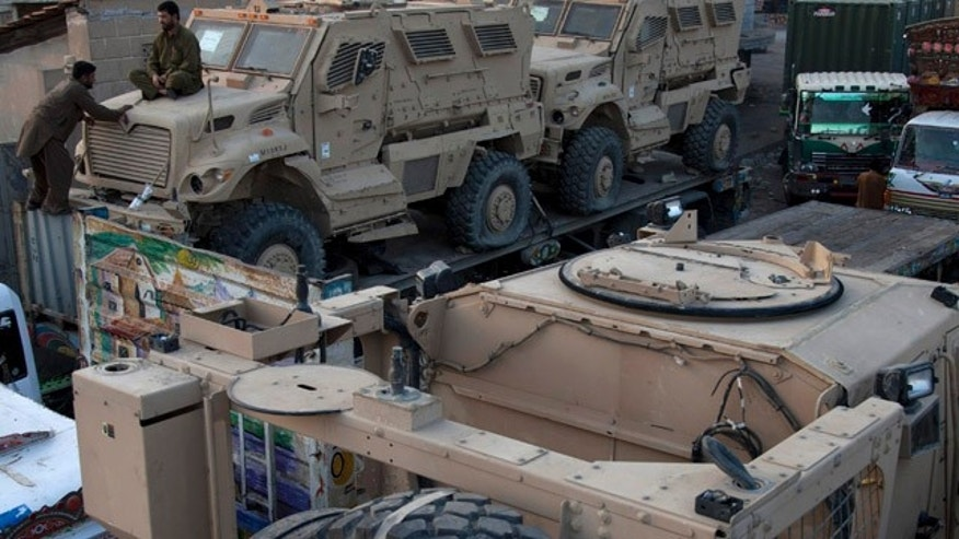 Nov. 26, 2013: A Pakistani man sits on a NATO military vehicle, carried with other vehicles on trucks at a terminal in Karachi, Pakistan.