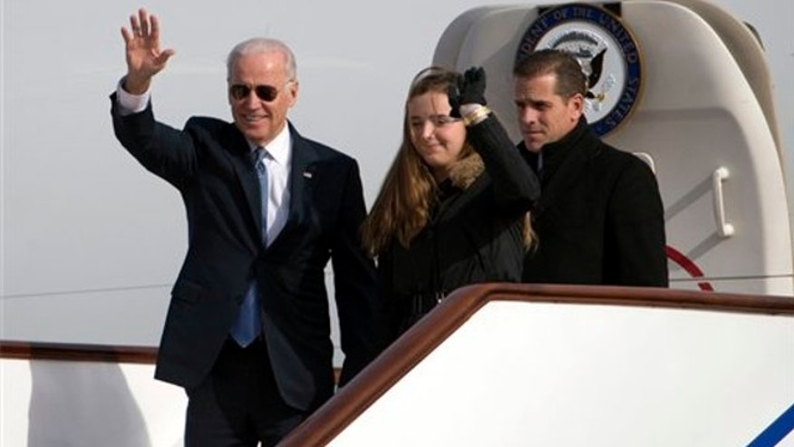 Dec. 4, 2013: Vice President Joe Biden, left, waves as he walks out of Air Force Two with his granddaughter Finnegan Biden and son Hunter Biden at the airport in Beijing, China.