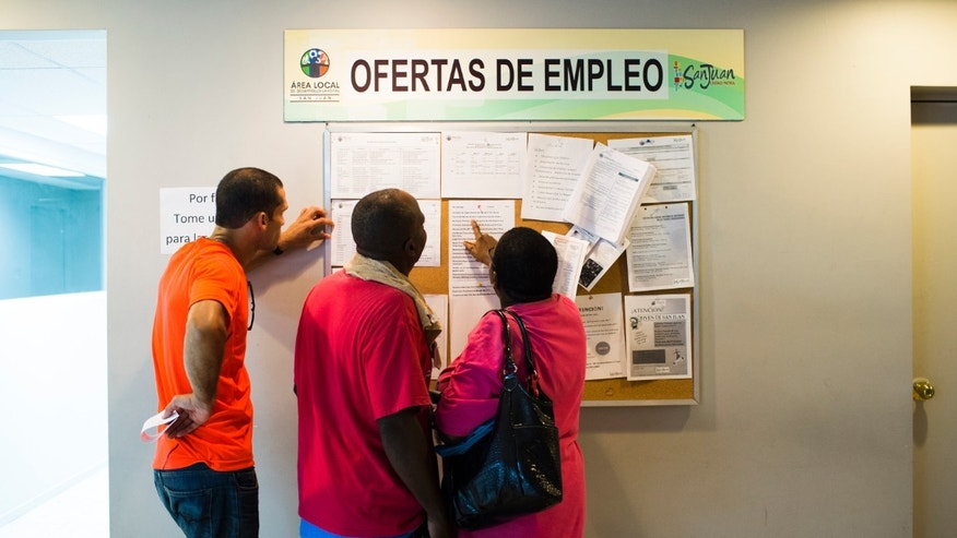 People scan the bulletin board for job postings at the unemployment office on November 14, 2013  in San Juan, Puerto Rico. The unemployment rate hovers around 14 percent, almost twice the national average.
