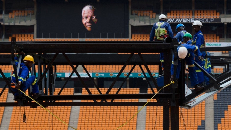An image of former South African President Nelson Mandela is shown on a big screen as work is carried out to put up a stage at the FNB stadium where his memorial service will take place on Tuesday, in Johannesburg, South Africa.