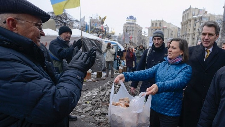 Dec. 11, 2013: U.S. Assistant Secretary for European and Eurasian Affairs Victoria Nuland offers food to pro-European Union activists as she and U.S. Ambassador to Ukraine Geoffrey Pyatt, right, walk through Independence Square in Kiev, Ukraine.