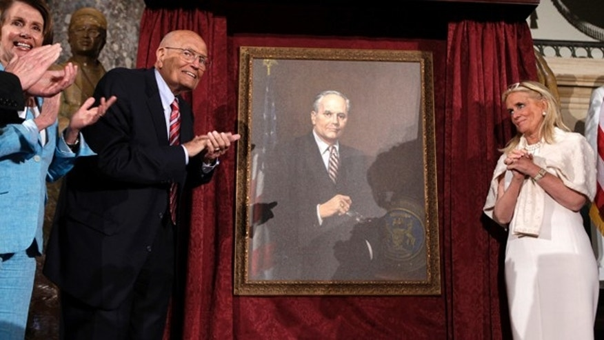 June 13, 2013: House Democratic Leader Nancy Pelosi (D-CA) (L), Representative John Dingell (D-MI) and his wife Deborah Dingell unveil Dingell's portrait as the longest serving member of Congress during an event on Capitol Hill in Washington.