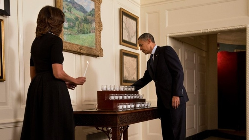Saturday, Dec. 14, 2013: President Obama and first lady Michelle Obama light candles in honor of the Newtown shooting victims, in the Map Room of the White House in Washington, D.C.
