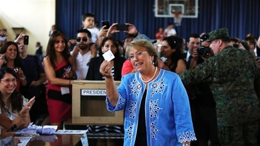 Presidential candidate and former President Michelle Bachelet holds up her vote before casting it during presidential elections in Santiago, Chile, Sunday, Dec. 15, 2013. Bachelet, 62, left office with sky-high approval ratings after her 2006-2010 presidency. (AP Photo/Jorge Saenz)