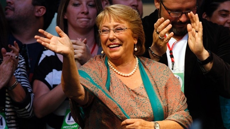Presidential candidate Michelle Bachelet waves during a victory rally in Santiago, Chile, Sunday, Dec. 15, 2013. With 90 percent of the votes counted, Bachelet had an unbeatable 62 percent to 38 percent for the center-right's Evelyn Matthei, who has conceded defeat. (AP Photo/Luis Hidalgo).