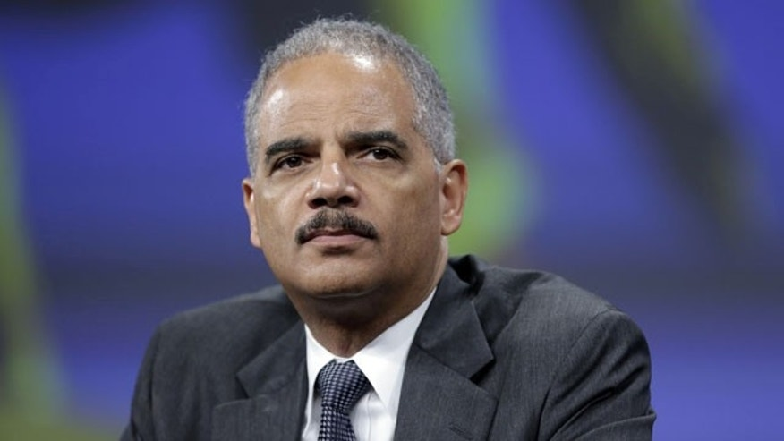 FILE - In this Oct. 21, 2013 file photo, Attorney General Eric Holder listens to a speech after of his remarks during the Annual International Association of Chiefs of Police Conference, at the Pennsylvania Convention Center in Philadelphia. (AP Photo)