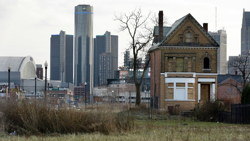 Dec. 2, 2013: An empty field in Brush Park, north of Detroit's downtown is shown with an abandoned home.