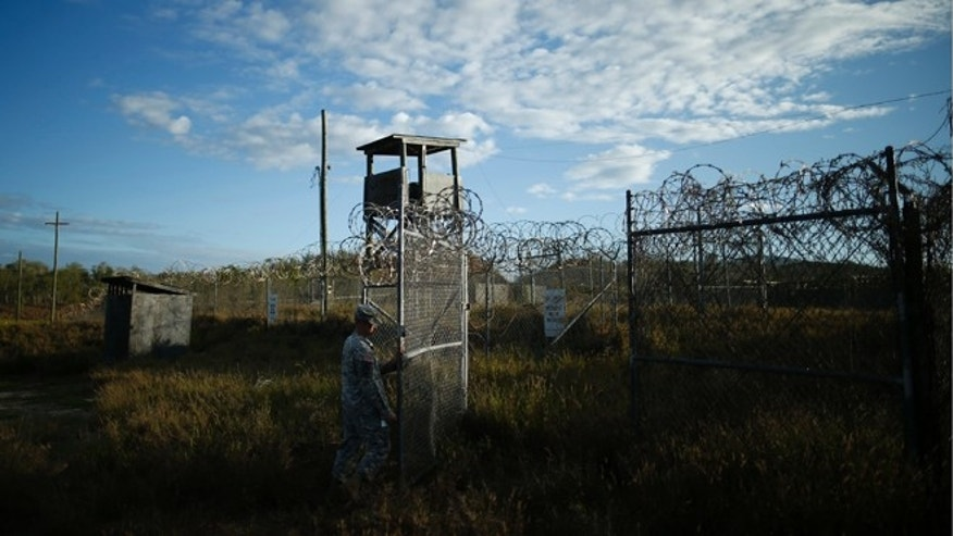 Nov. 21, 2013: In this photo reviewed by the U.S. military, a soldier closes the gate at the now-abandoned Camp X-Ray, which was used as the first detention facility for Al Qaeda and Taliban militants who were captured after the Sept. 11 attacks at Guantanamo Bay Naval Base, Cuba.