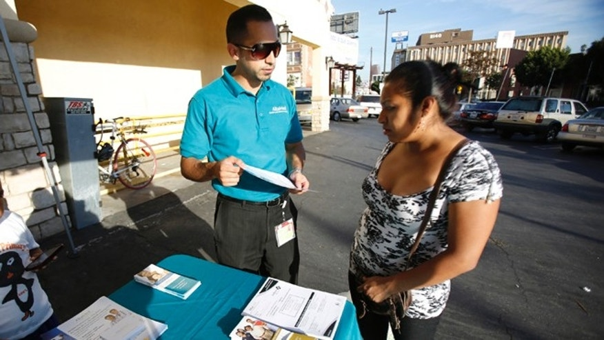 FILE: Nov. 6, 2013: A patient care coordinator at AltaMed, speaks to a woman during a community outreach on Obamacare in Los Angeles, Calif.