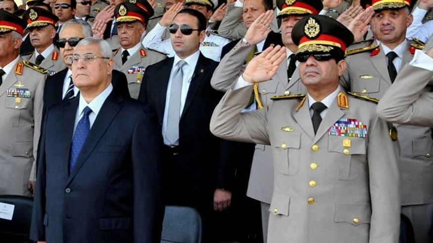 In this July 22, 2013, file photo released by the Egyptian Presidency, Egypt's interim President Adly Mansour, left, standing next to Defense Minister Gen. Abdel-Fattah el-Sissi, listens to the national anthem during a medal ceremony at a military base east of Cairo.
