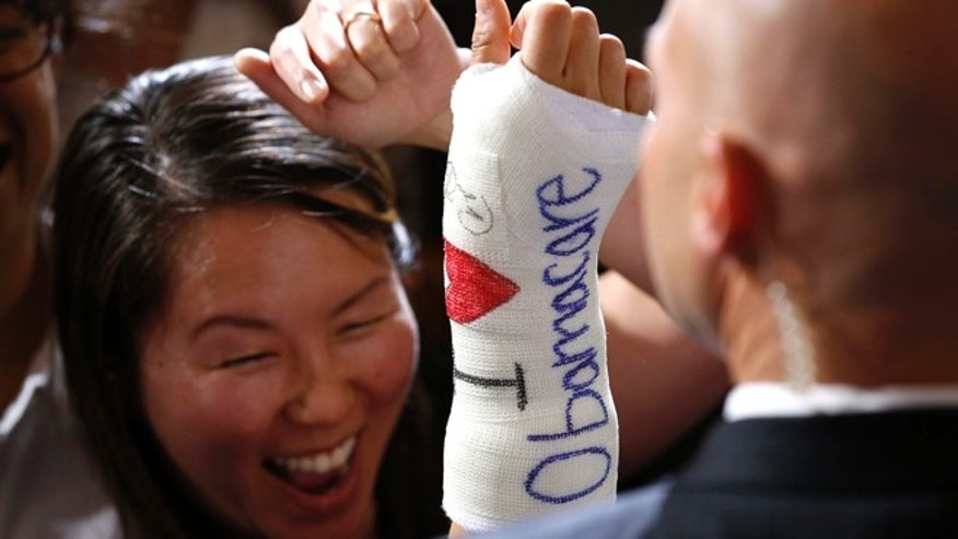 FILE: October 30, 2013: A Massachusetts woman after President Obama signed her cast in Boston, Mass.