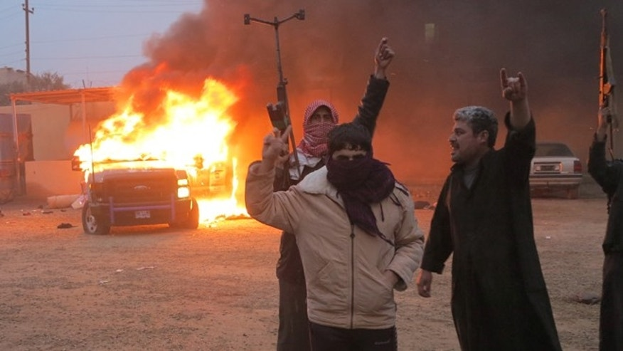 FILE: December 31, 2013: Protesters burn a police vehicle during fighting in Ramadi, in Iraq.