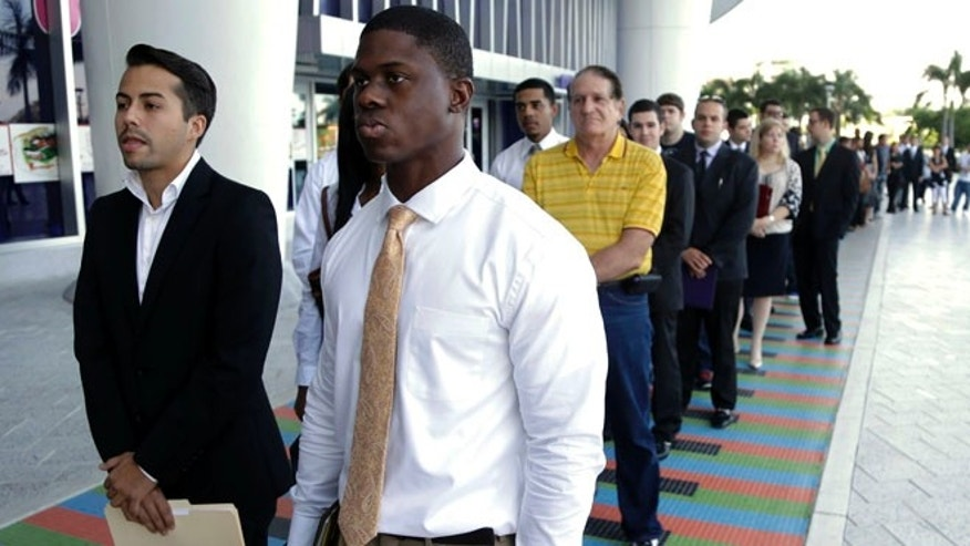 Oct. 23, 2013 file photo of Luis Mendez, 23, left, and Maurice Mike, 23, in line at a job fair held by the Miami Marlins, at Marlins Park in Miami.
