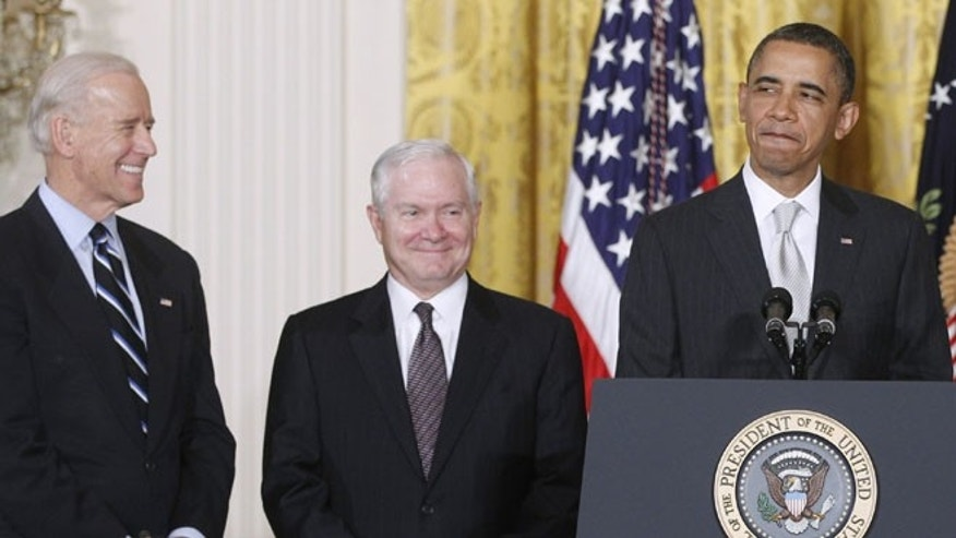 In this April 28. 2011 file photo, President Obama stands in the East Room of the White House in Washington with Vice President Biden and  then-outgoing Defense Secretary Robert Gates.