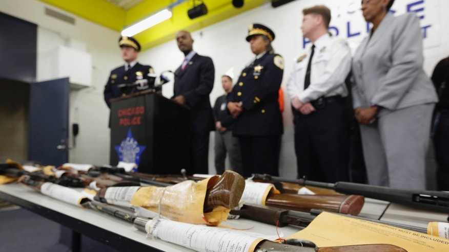 FILE - In this Jan. 28, 2013, file photo, Chicago Police First Deputy Superintendent Alfonsa Wysinger, second from left, speaks at a news conference in Chicago with a display of recently seized guns, part of the 574 that had been seized in the city since Jan. 1. The mounting homicide toll in President Barack Obamas hometown has giving ammunition to both sides in the nations debate about gun rights and safety. On Monday, Jan. 6, 2014, a federal judge in Chicago potentially opened a new market to gun dealers after ruling as unconstitutional Chicago ordinances that aim to reduce gun violence by banning their sale within the city&#39&#x3b;s limits. (AP Photo/M. Spencer Green, File)