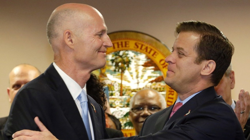 Florida Gov. Rick Scott, left, congratulates Miami-Dade Property Appraiser Carlos Lopez-Cantera after naming him lieutenant governor and his running mate for 2014, during a news conference, Tuesday, Jan. 14, 2014 in Miami. (AP Photo/Wilfredo Lee)