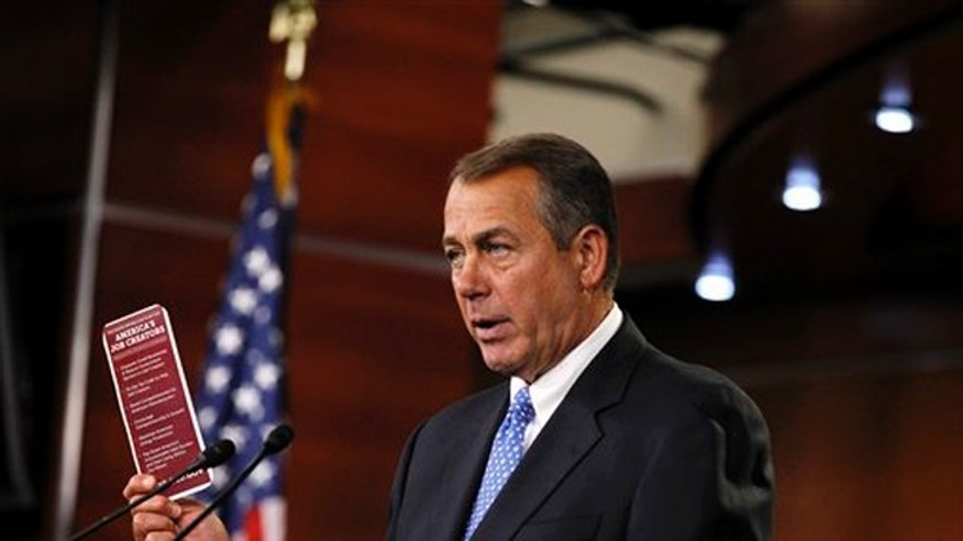 House Speaker John Boehner, R-Ohio,  holds a job brochure during a news conference on Capitol Hill in Washington.