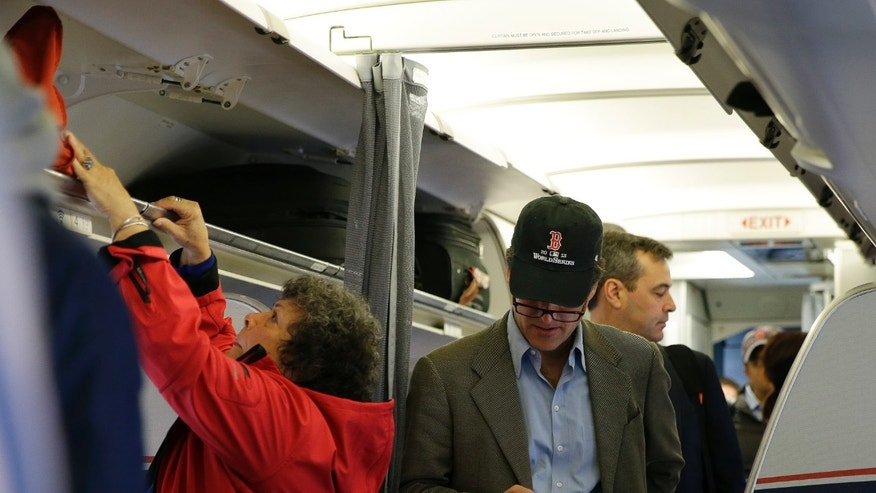 Oct. 31, 2013: A passenger checks his cell phone while boarding a flight in Boston.