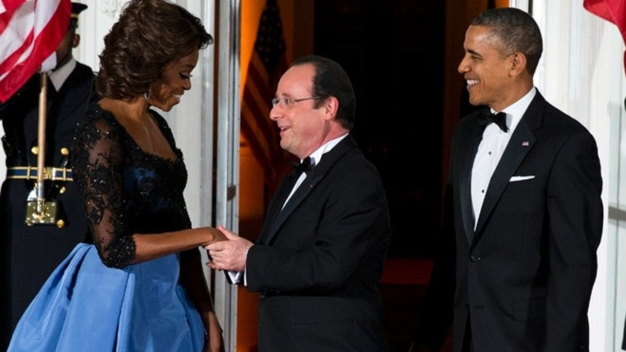 Feb. 11, 2014: First lady Michelle Obama, left, and President Barack Obama welcome French President François Hollande for a State Dinner at the North Portico of the White House in Washington.