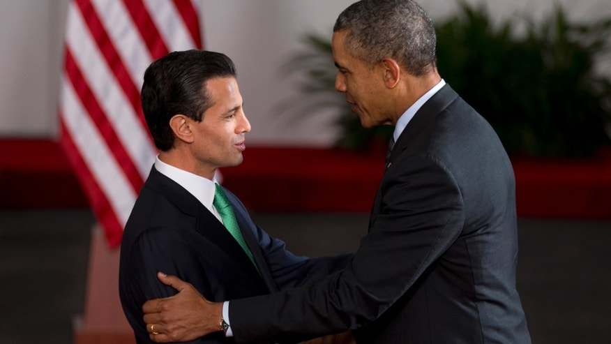 Mexico's President Enrique Pena Nieto, left, and President Barack Obama shake hands upon Obama's arrival to the North American Leaders Summit in Toluca, Mexico Wednesday, Feb. 19, 2014. Obama is in Toluca Wednesday for the one-day summit with Mexican and Canadian leaders, meeting on issues of trade and other neighbor-to-neighbor interests, even as Congress is pushing back against some of his top cross-border agenda items. (AP Photo/Eduardo Verdugo)