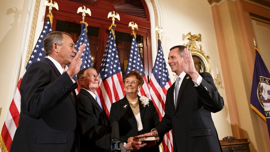 March 13, 2014: Newly elected Republican Rep. David Jolly of Florida, right, poses during a ceremonial swearing-in with House Speaker John Boehner of Ohio, left, on Capitol Hill in Washington.