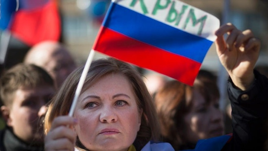 "March 10, 2014: A woman with a Russian flag that reads ""Crimea"" amid demonstrators for Russians in Crimea, Moscow, Russia."