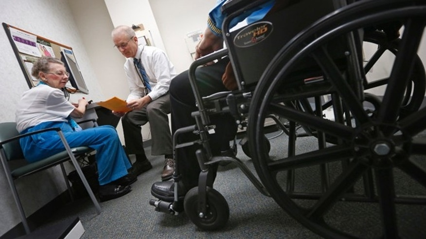 Nov. 26, 2013: A doctor speaks to patients at his office in Peoria, Ill.