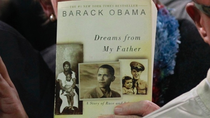 "FILE: A member of the audience waits with her copy of President  Obama's book ""Dreams from my Father"" as Obama  meets workers in the audience following remarks at Linamar Corporation."