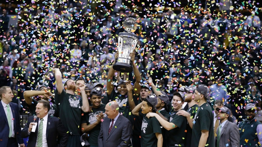 Mar. 16, 2014: Michigan State players and coaches celebrate after they defeated Michigan 69-55 in an NCAA college basketball game in the championship of the Big Ten Conference tournament.