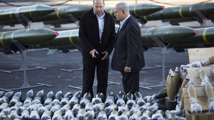 March 10, 2014: Israel's Prime Minister Benjamin Netanyahu, right, and Israel's Defense Minister Moshe Yaalon, left, examine dozens of mortar shells and rockets on display after being seized from the Panama-flagged KLOS C civilian cargo ship that Israel intercepted last Wednesday off the coast of Sudan, at a military port in the Red Sea city of Eilat, southern Israel.