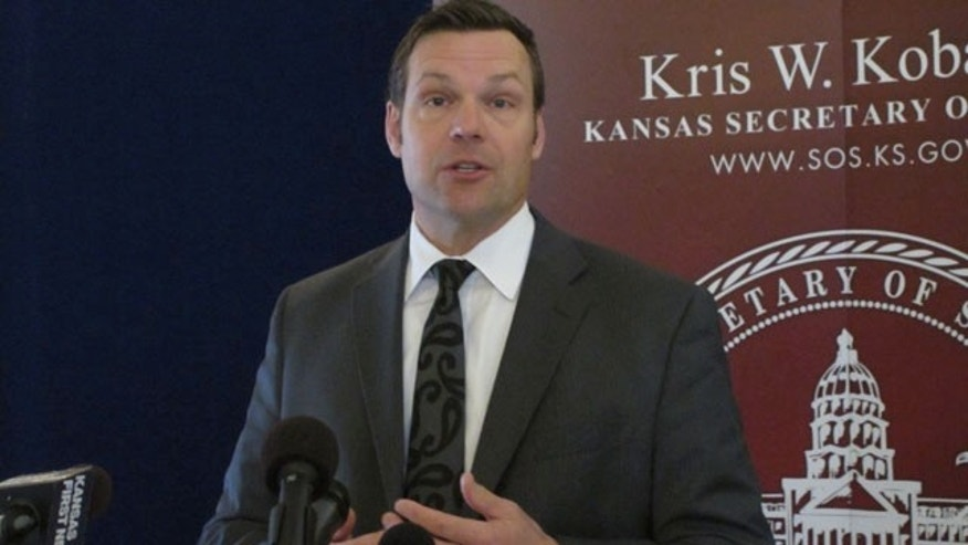 March 19, 2014: Kansas Secretary of State Kris Kobach discusses a federal judge's ruling ordering the federal government to help Kansas and Arizona enforce their proof-of-citizenship requirements for new voters. Kobach and Arizona Secretary of State Ken Bennett filed a lawsuit over the issue. (AP Photo/John Hanna)