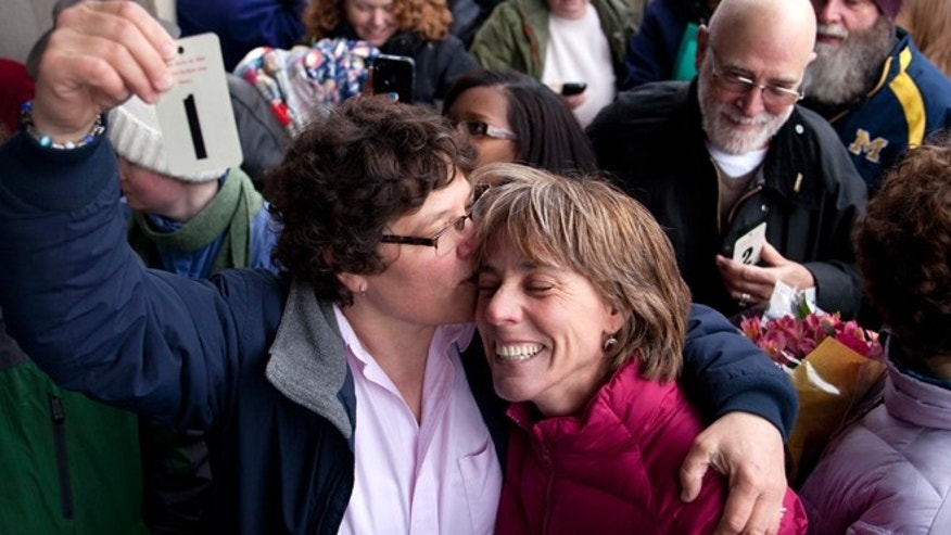 Mar. 22, 2014: Elizabeth Patten, left, holds up the first marriage ticket to marry her partner Johnnie Terry in front of the Washtenaw County Clerks office in Ann Arbor, Mich.