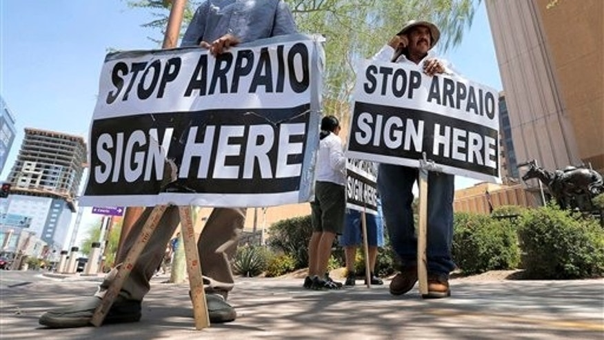 FILE - In this May 29, 2013, file photo, Simon Lopez, left, and Hiliaro Islas hold signs while trying to collect signatures in an effort to recall Maricopa County Sheriff Joe Arpaio, in downtown Phoenix. Arizona is still widely viewed in Mexico as the most anti-Mexico state in the U.S., even if the tough anti-migrant law behind that perception has been largely voided. But Arizonas leaders are logging lots of miles to put a new face on their home state. (AP Photo/Matt York, File)