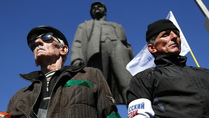 March 23, 2014: Activists stand guard during a pro Russian rally at a central square in Donetsk, eastern Ukraine. About 5,000 people demonstrated in Donetsk in favor of holding a referendum on secession and absorption into Russia similar to Crimea's. A statue of Lenin is seen in the background. (AP Photo/Sergei Grits)