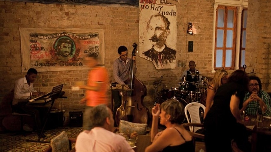 In this March 15, 2014 photo, people attend the private club Cafe Madrigal in Havana, Cuba.