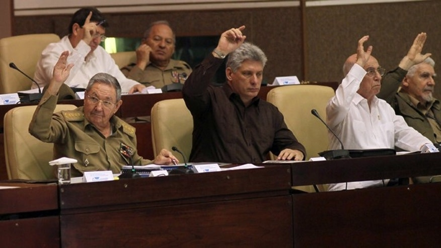 Cuba'ss Vice-President Miguel Díaz-Canel,  center,  Cub's President Raúl Castro, left,  First Vice-President of the Council of State José Ramón Machado Ventura, second from right,  and Commander of the Cuban Revolution Ramiro Valdes, right,  raise their hands to vote the foreign investment law during an extraordinary session at the National Assembly in Havana, Cuba, Saturday, March. 29, 2014. Cuban lawmakers approved a law Saturday that aims to make it more attractive for foreign investors to do business in and with the country, a measure seen as vital if the island's struggling economy is to improve. IN the back row, also voting, Foreign Minster Bruno Rodrigues, left, and Defense Minister Leopoldo Cintas Frias, right. (AP Photo/Ismael Francisco, Cubadebate)