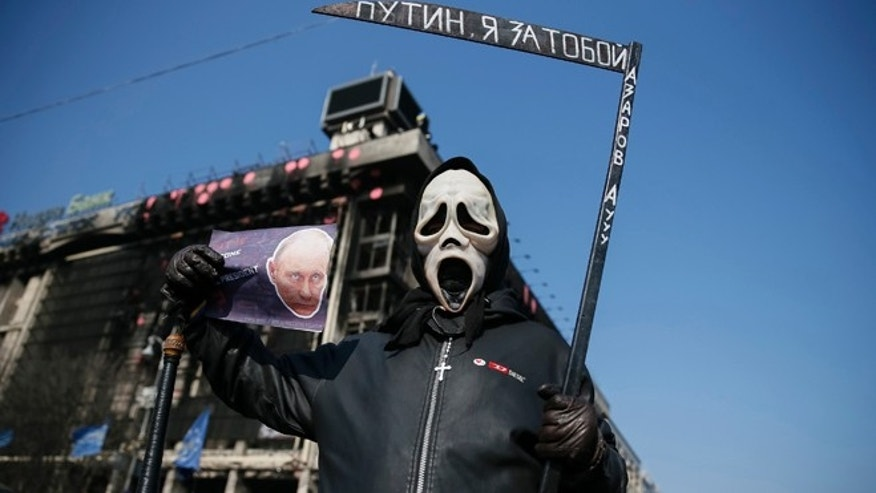 March 23, 2014: An anti-war rallier with a sign depicting Russian President Vladimir Putin, Independence Square, in Kiev, Ukraine.