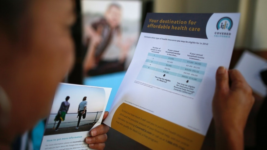 Kay Campos, 56, who has no health insurance and diabetes, browses leaflets at a Covered California event which marks the opening of the state's Affordable Healthcare Act.